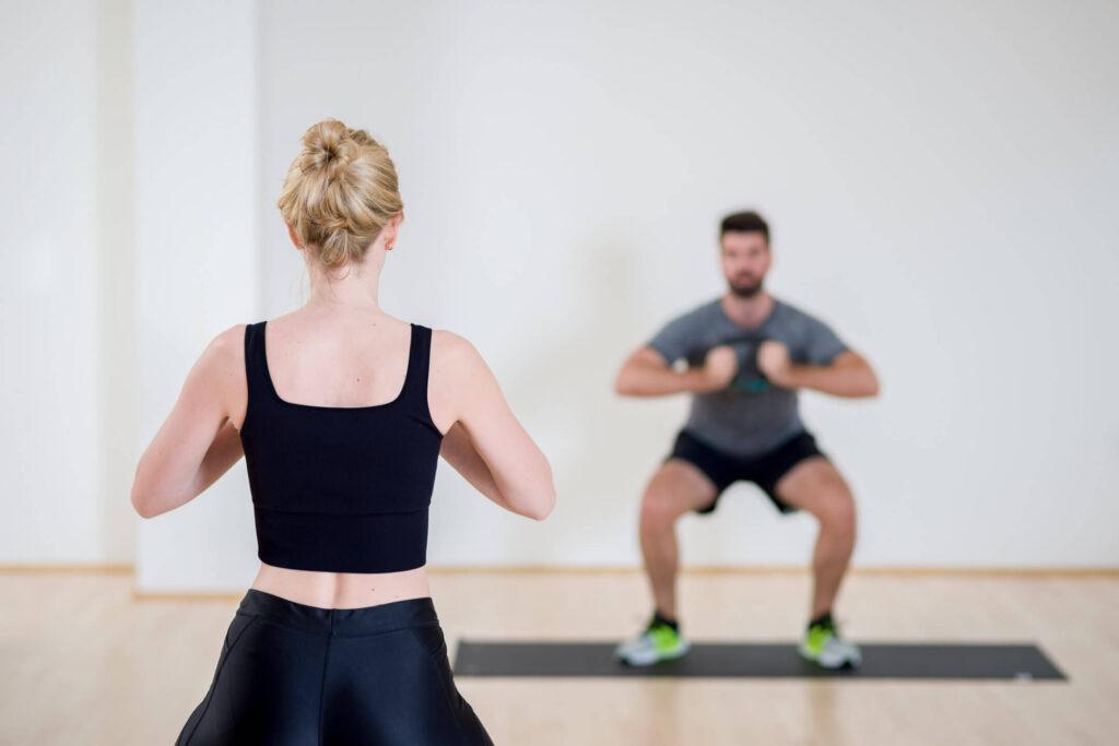 Personal Training von Dr. Ju, Gewichte werden zur Fitness vor der Brust gehalten